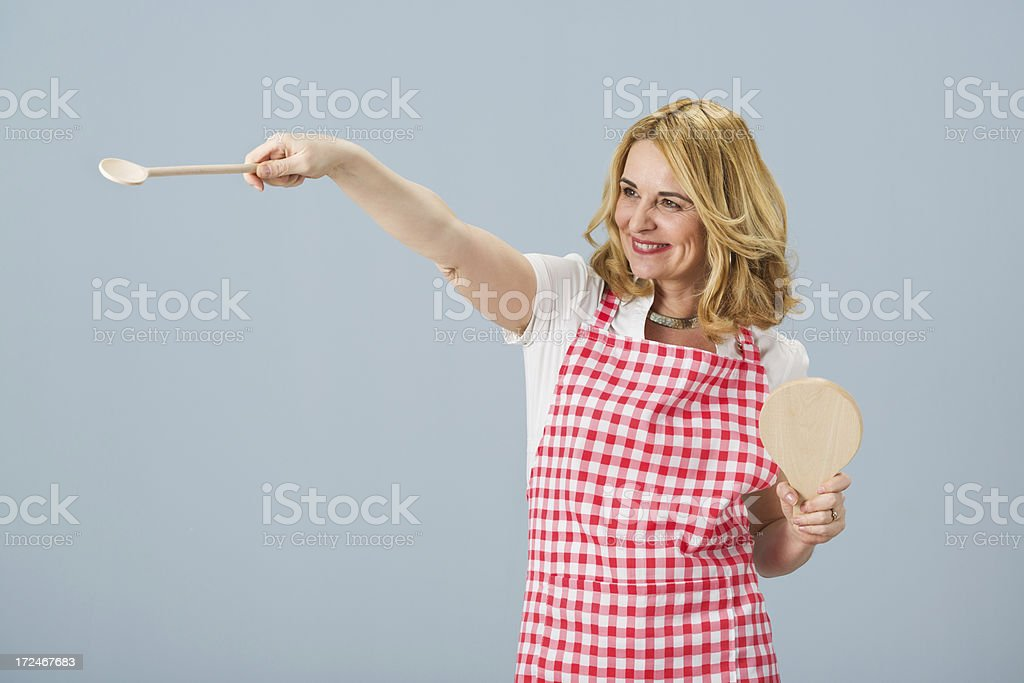 Woman wearing apron holding wooden spoon and plank royalty-free stock photo