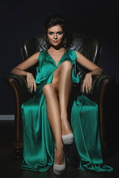 Woman wearing beautiful green silk dress is posing on leather couch stock photo