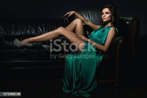 Sexy woman wearing beautiful green silk dress is posing on leather couch