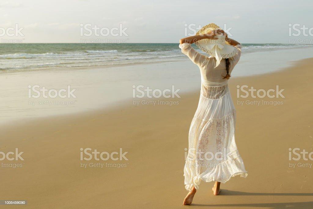 dbca5c3326 Woman wearing beautiful white dress is walking on the beach during sunset  royalty-free stock