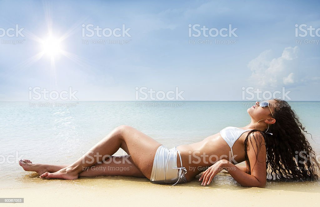 Woman wearing bikini and lying on sandy beach in summer stock photo