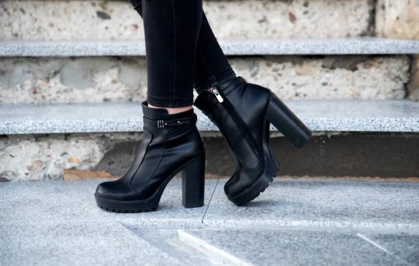 vistiendo botas negras de mujer - bota fotografías e imágenes de stock