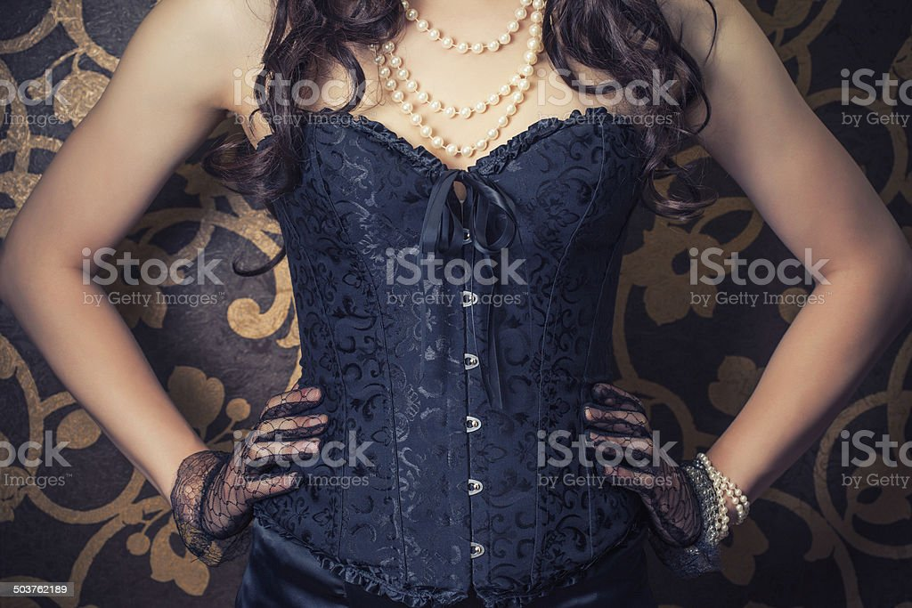woman wearing black corset and pearls against retro background stock photo