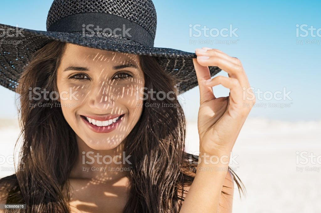 Woman wearing black hat at beach Portrait of beautiful young woman wearing summer black hat with large brim at beach. Closeup face of attractive girl with black straw hat. Happy latin woman smiling and looking at camera with sea in background. Adult Stock Photo