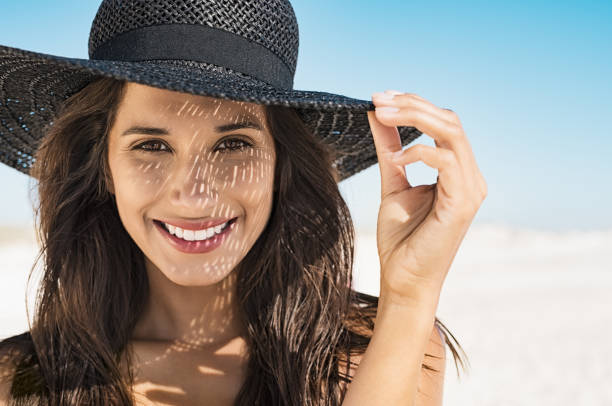 woman wearing black hat at beach - luce solare foto e immagini stock