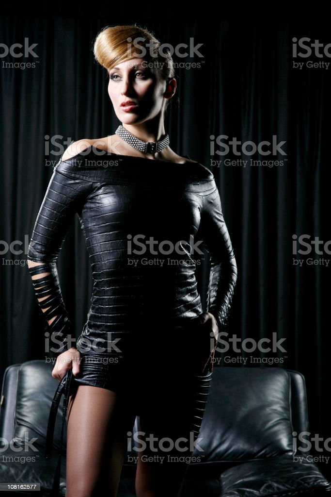 Woman Wearing Black Leather Dress and Posing, Low Key royalty-free stock photo
