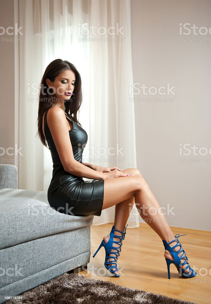 woman wearing black leather short dress sitting on bed stock photo
