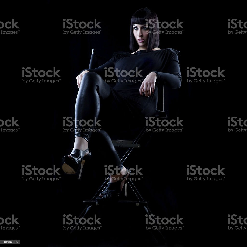 Woman wearing black sits in director's chair with smug look stock photo