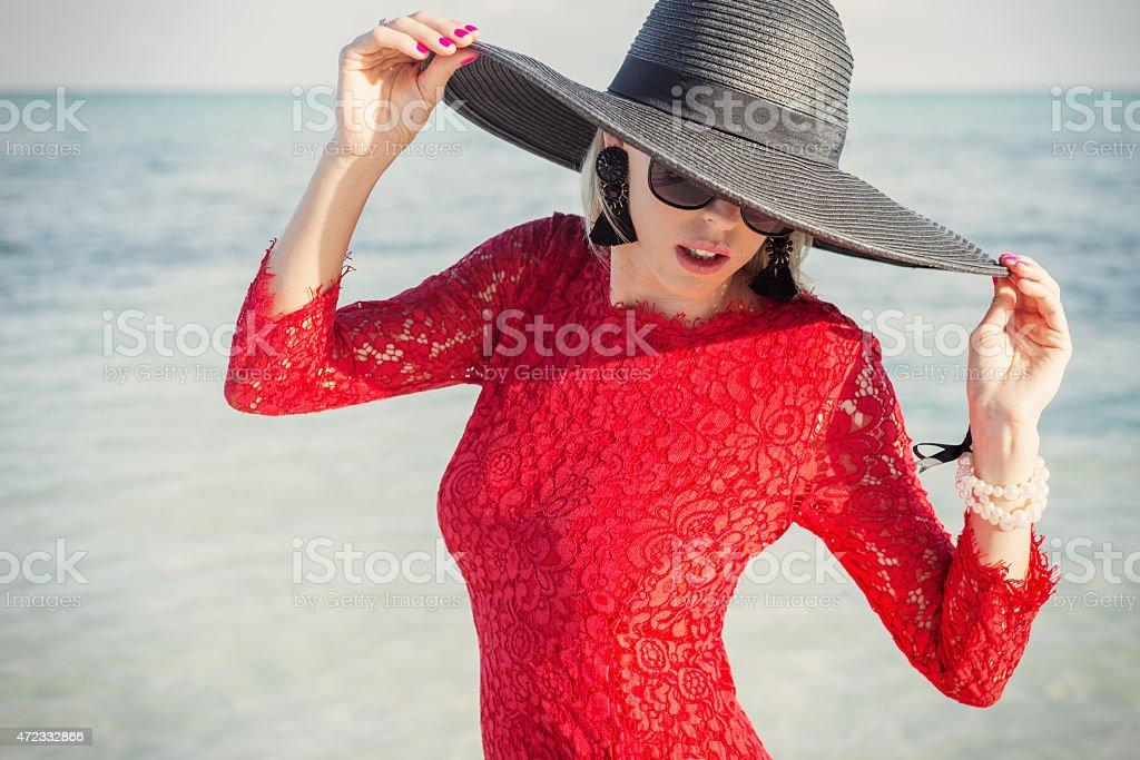 b4fcdc8fd74d Donna con nero cappello e abito Rosso estivo sulla spiaggia foto stock  royalty-free