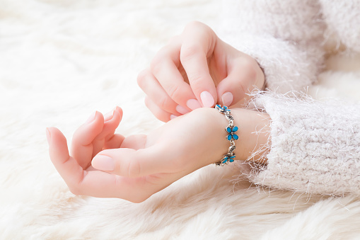 istock Woman wearing blue flower bracelet on her hand wrist on white, fluffy blanket. Closeup. 1083779318