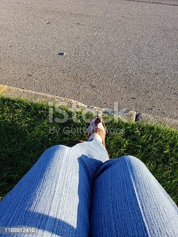 Relaxing by the road is a woman sitting in blue Jean's and leather sandals
