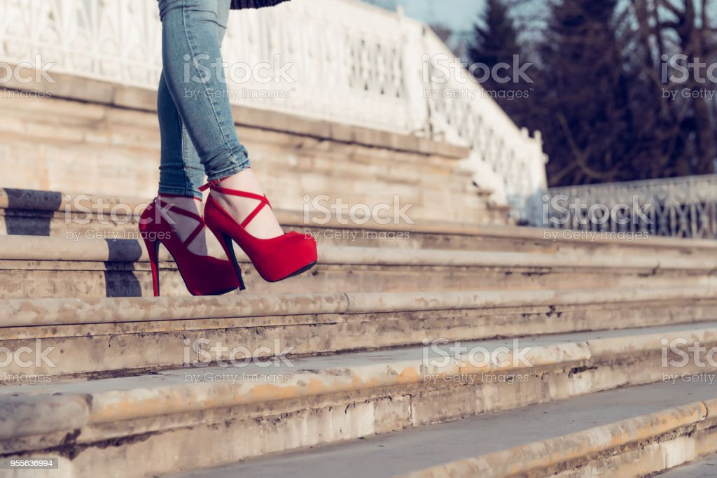 Detail close up of woman legs in blue jeans and red high heel...