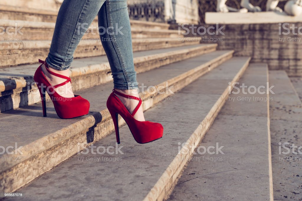 Woman wearing blue jeans and red high heel shoes in old town. The women wear high heels walk down stairs. Sexy legs in red high heel shoes. Trendy fashion look stock photo
