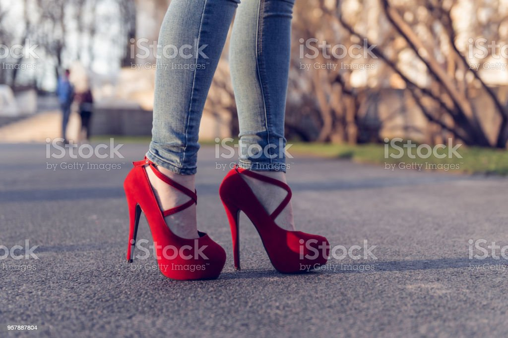 Woman wearing blue jeans and red high heel shoes. The women wear high heels standing on the road. Sexy legs in red high heel shoes. Trendy fashion look stock photo