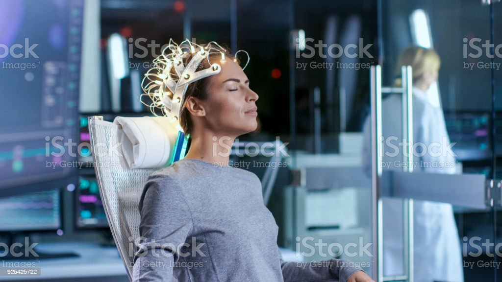 Woman Wearing Brainwave Scanning Headset Sits in a Chair while Scientist Supervises. In the Modern Brain Study Laboratory Monitors Show EEG Reading and Brain Model. stock photo