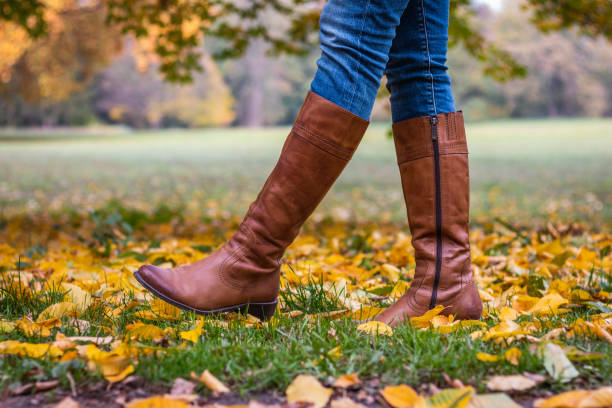 Woman wearing brown leather boot and walking in fallen leaves. Fashion model in autumn park boot stock pictures, royalty-free photos & images
