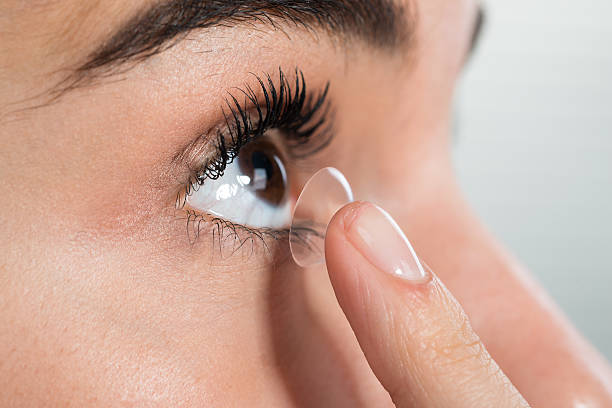 Woman Wearing Contact Lens At Home Closeup of young woman wearing contact lens at home inserting stock pictures, royalty-free photos & images