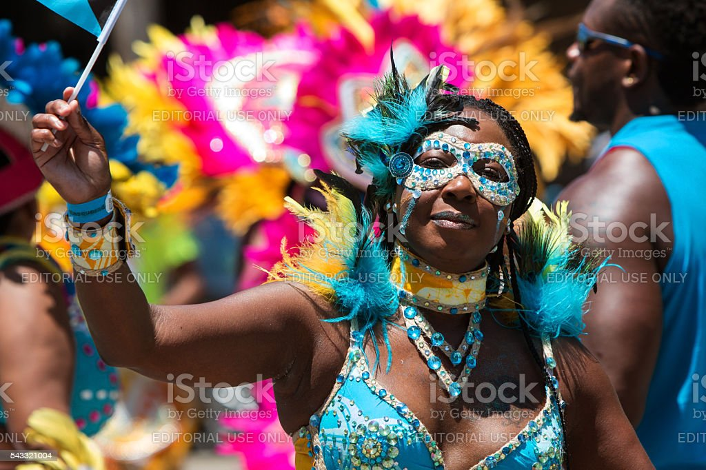 A woman wearing an elaborate costume and mask participates in a...