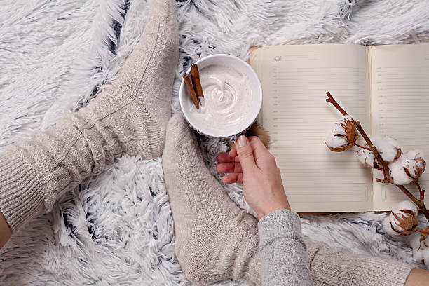 Woman wearing cozy warm wool socks, reading a book stock photo