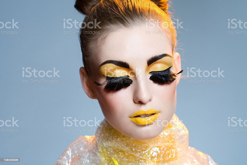 Woman Wearing Crazy Yellow Make-up and Feather Eyelashes royalty-free stock photo