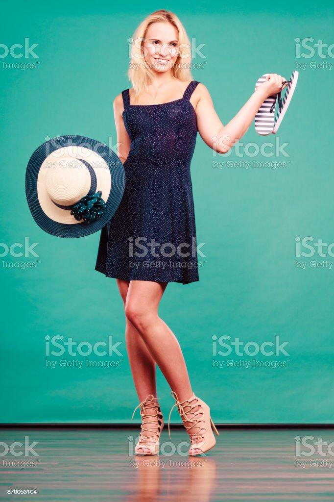 4cd00860a65b Woman wearing dress holding sun hat an flip flops foto stock royalty-free