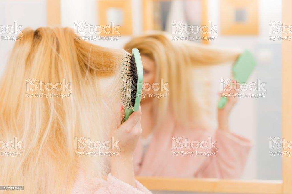 Woman wearing dressing gown brushing her hair stock photo