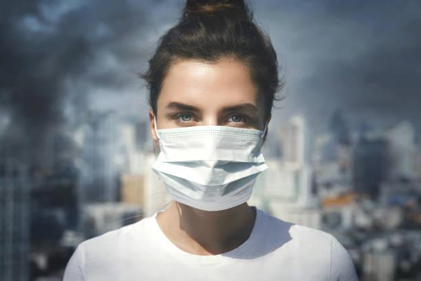 mujer con mascarilla debido a la contaminación del aire en la ciudad - contaminación ambiental fotografías e imágenes de stock