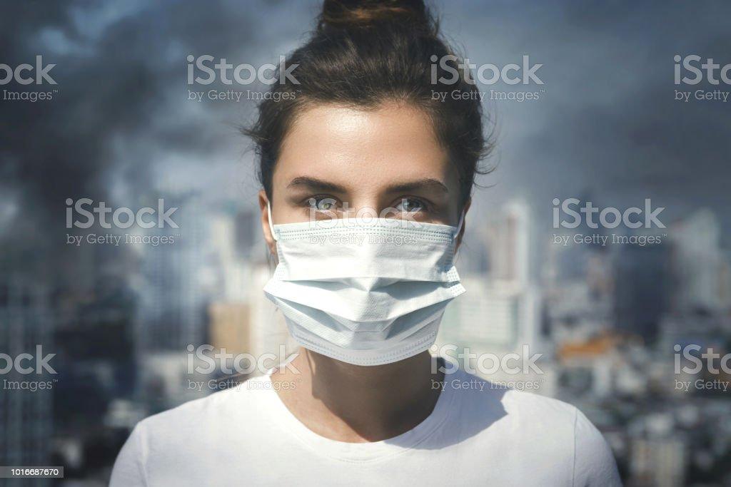 Mujer con mascarilla debido a la contaminación del aire en la ciudad - foto de stock