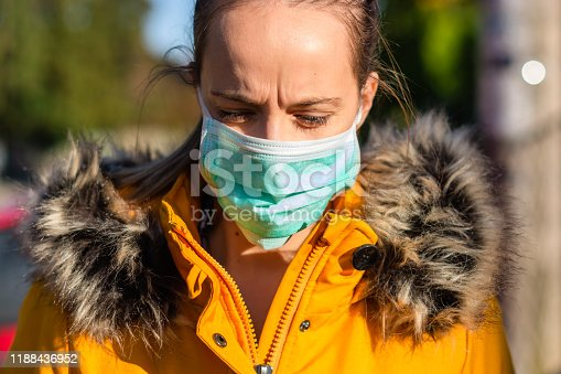 Young woman walking on the road with flu mask.