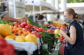 Blurred woman wear face mask is buying fresh fruits and vegetables on a farmer market in Sofia, Bulgaria on july 22, 2020.