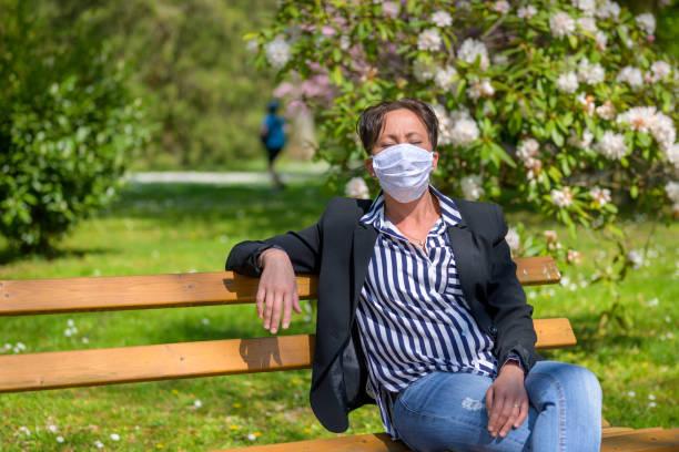 Woman wearing face mask enjoying the sunshine stock photo