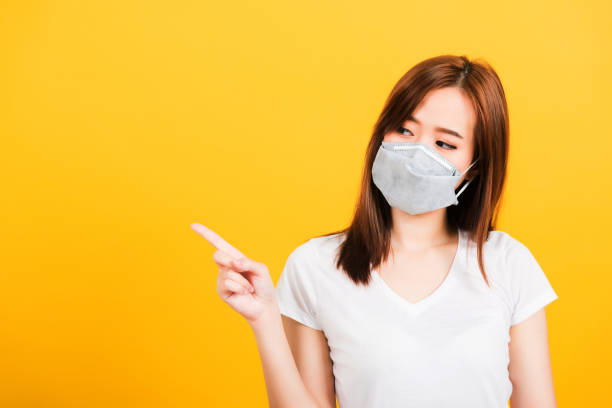 woman wearing face mask protects filter dust pm2.5 anti-pollution, anti-smog, and air pollution her pointing out to side Portrait Asian beautiful happy young woman wearing face mask protects filter dust pm2.5 anti-pollution, anti-smog, and air pollution her pointing out to side on yellow background, with copy space antipollution stock pictures, royalty-free photos & images