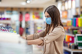 Woman wearing face mask push shopping cart in supermarket department store. Girl choosing, looking grocery things to buy at shelf during coronavirus crisis or covid19 outbreak.