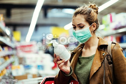 Young woman with protective mask reading label on the bottle while buying hand soap in the supermarket during virus epidemic.