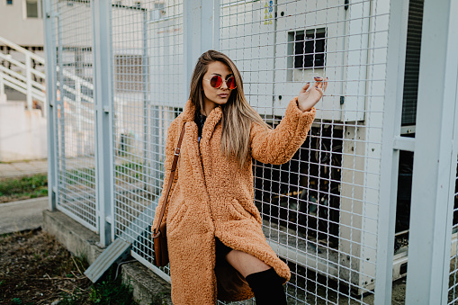 Beautiful young fashionable woman wearing fake fur coat enjoying a lovely autumn day in the city