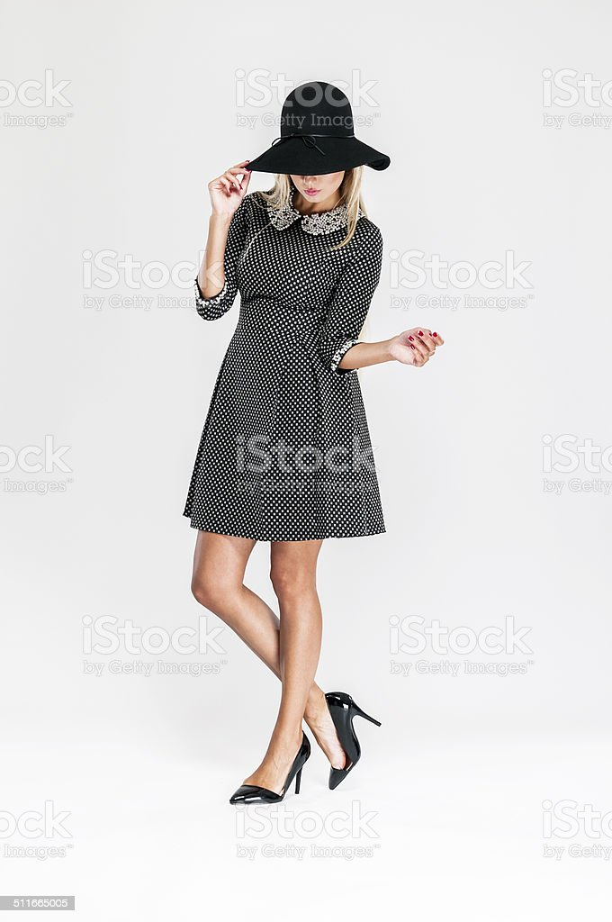 Woman wearing fashionable black dress in peas pattern, hat, pearls stock photo