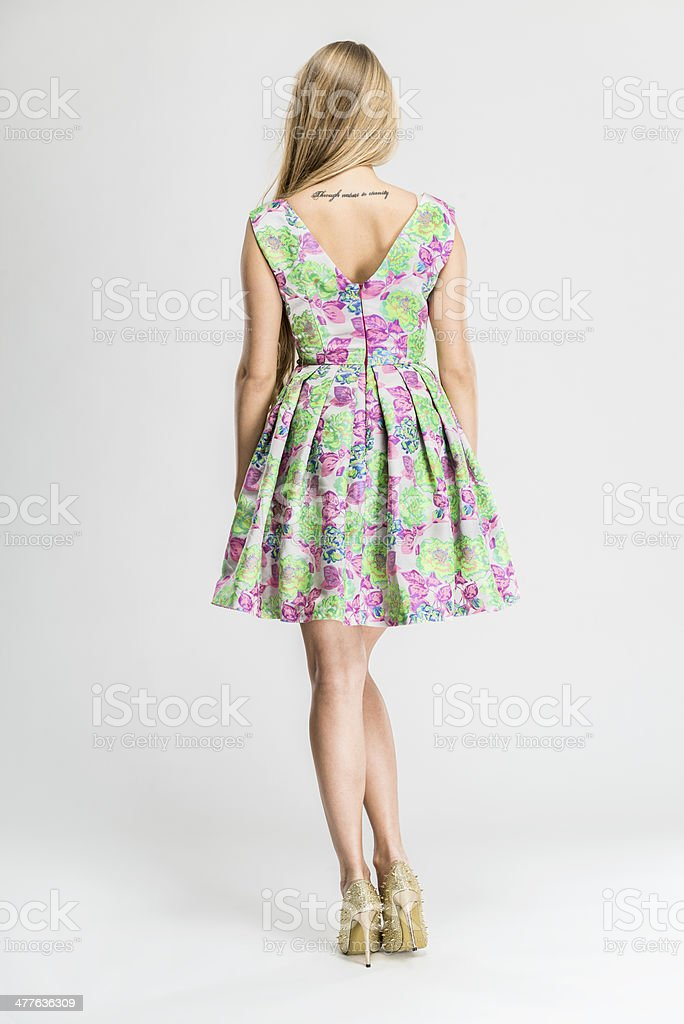Woman wearing fashionable sleeveless dress with floral design, rear view stock photo