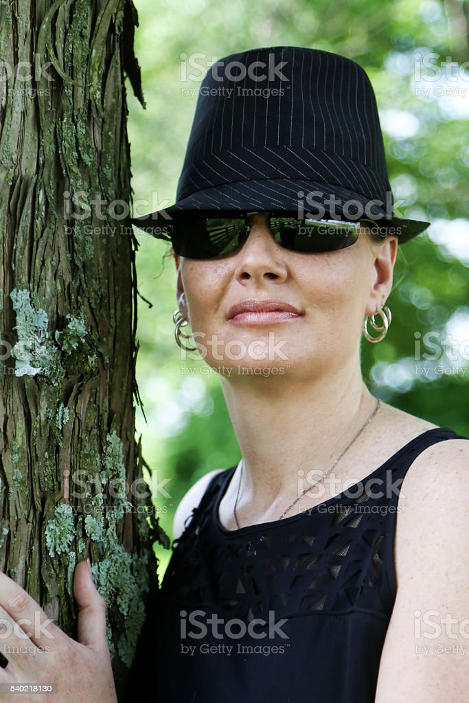 5cd1f73d Woman Wearing Fedora Hat and Sunglasses Poses Next to Tree royalty-free  stock photo