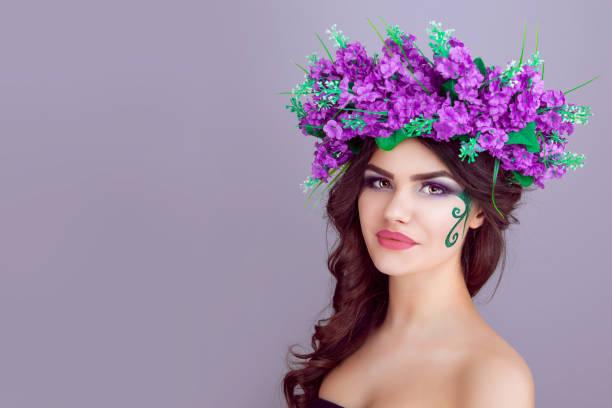 frau mit blumen auf lila hintergrund isoliert stirnband - lila augen make up stock-fotos und bilder