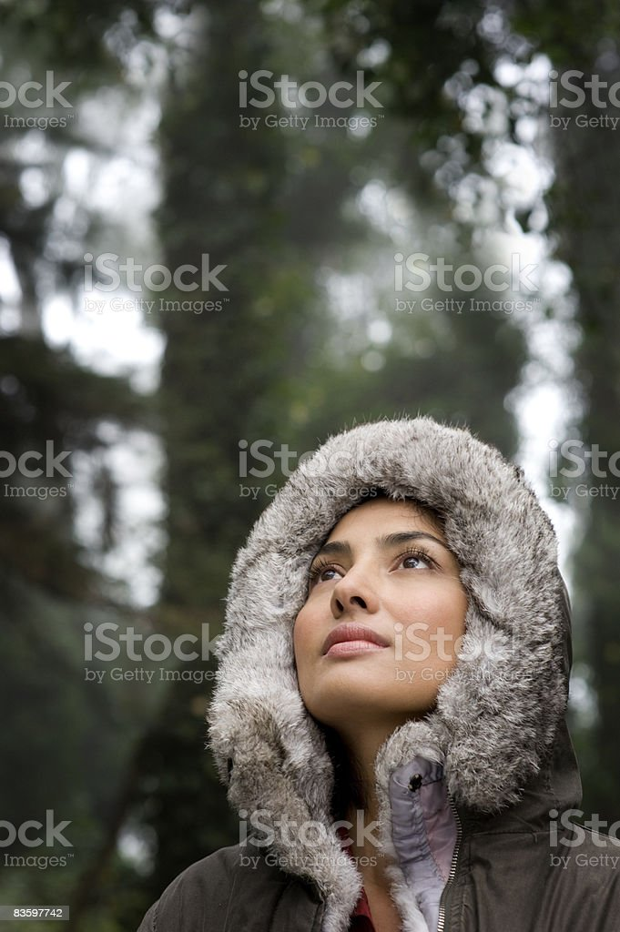 Woman wearing fur hood looking up royaltyfri bildbanksbilder