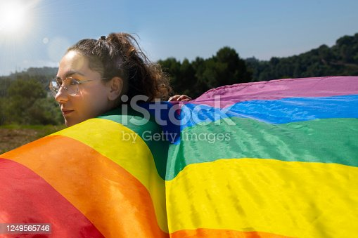 Woman wearing glasses holding rainbow waving flag outdoors. Lgtbiq concept.