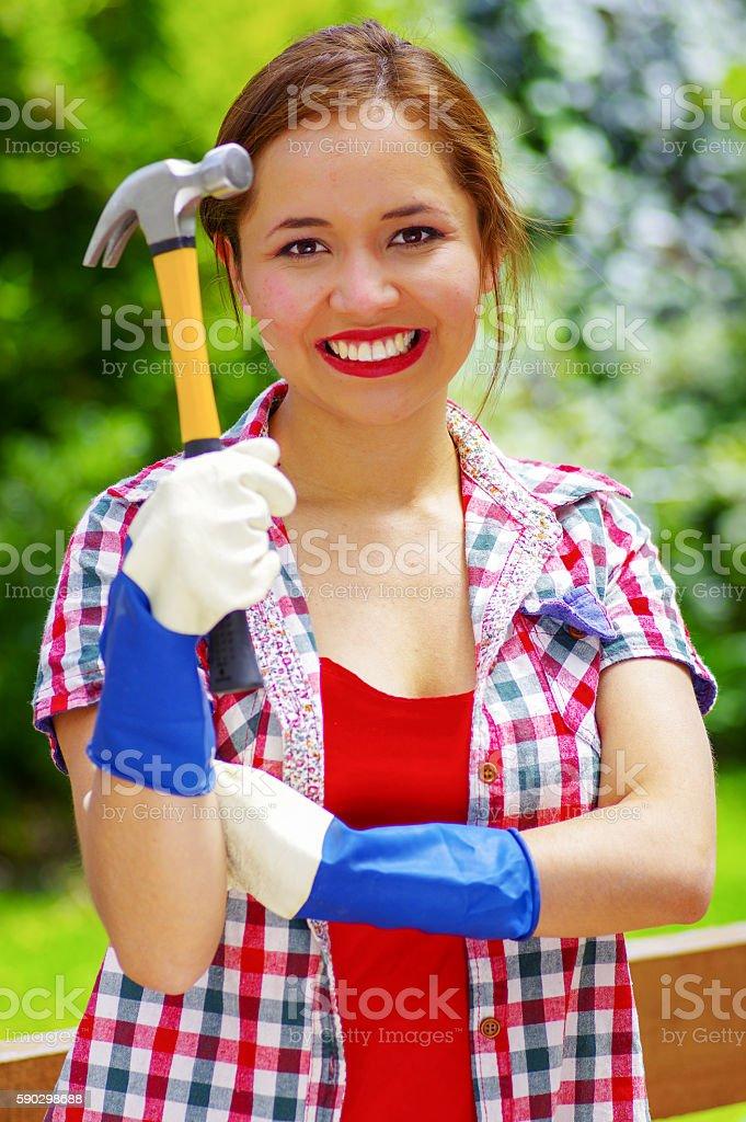 woman wearing gloves and holding a hammer royaltyfri bildbanksbilder