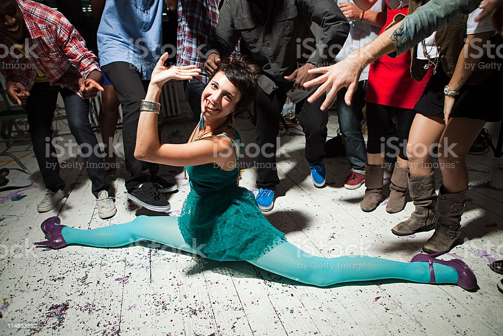 Woman wearing green dress at party doing the splits stock photo