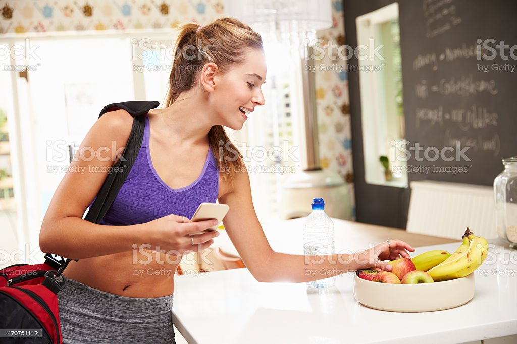 Woman Wearing Gym Clothing Choosing Fruit From Bowl stock photo