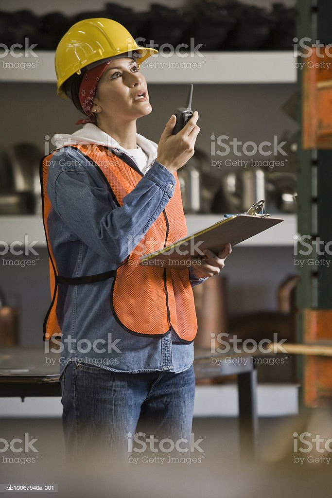 Woman wearing hard hat and safety vest, using walike talkie foto royalty-free