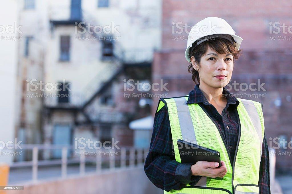 Woman wearing hard hat holding digital tablet foto