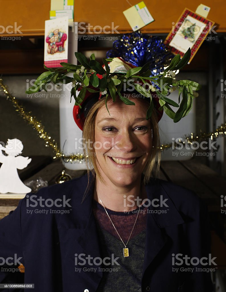 Woman wearing hard hat with mistletoe branch, smiling, portrait royalty-free stock photo