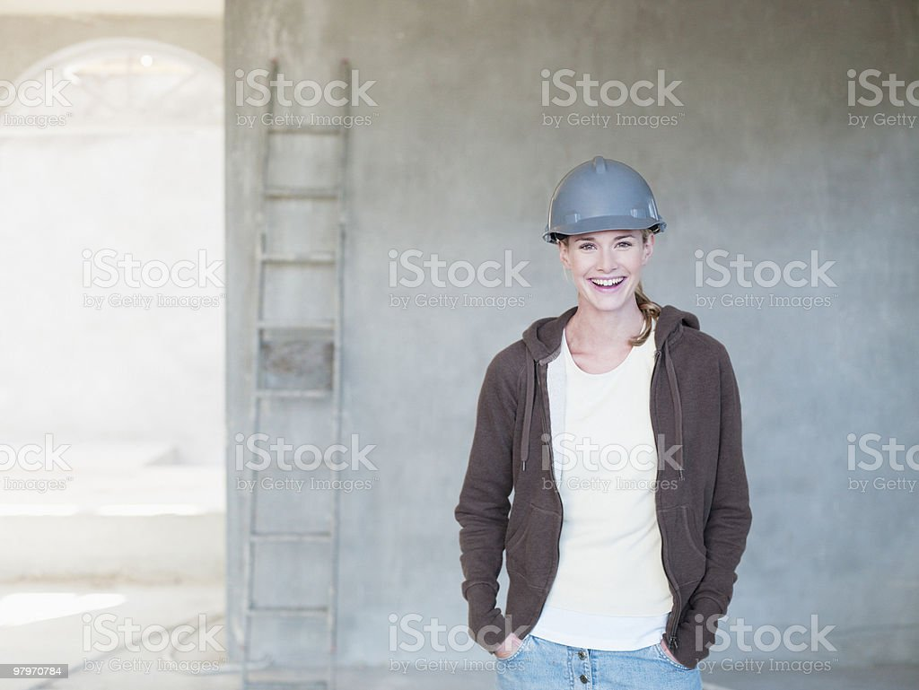 Woman wearing hard-hat inside house under construction royalty-free stock photo