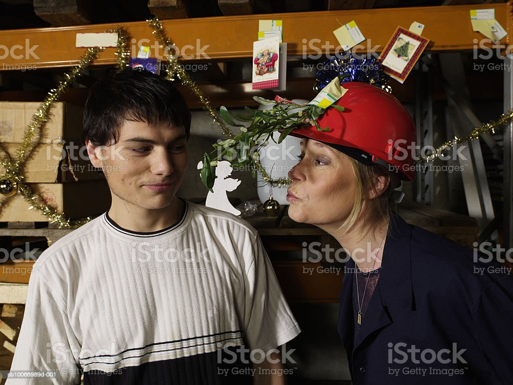 Woman wearing hat with misletoe branch trying to kiss young man in warehouse royalty free stockfoto