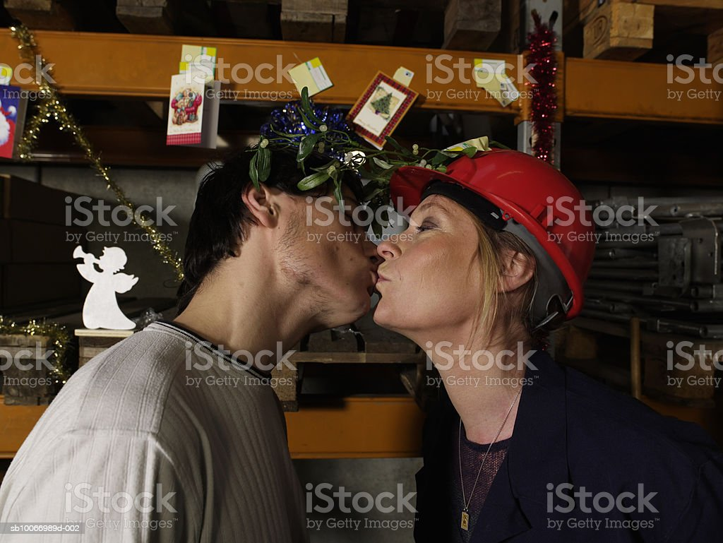 Woman wearing hat with misletoe kissing young man in warehouse, side view royalty free stockfoto